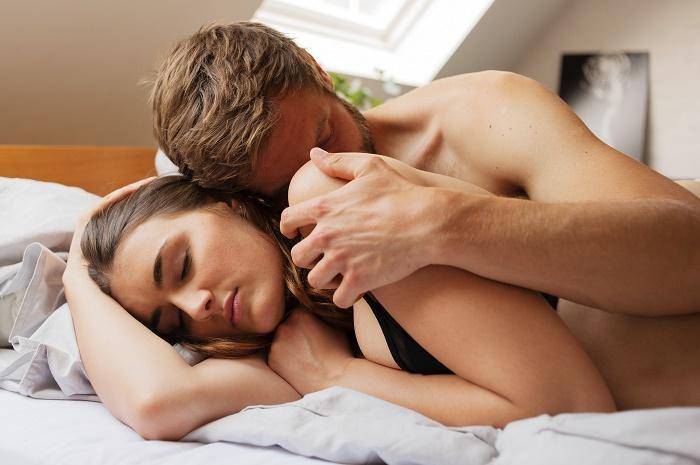 Pärchen im Bett, entspannt kuschelnd