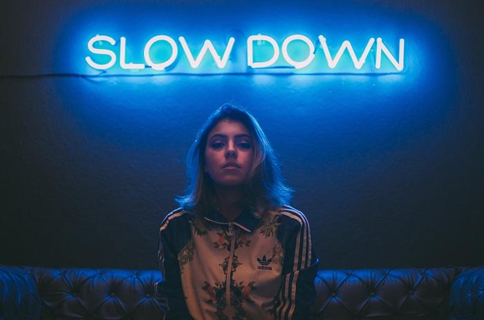 Slow down - Bild einer Person, die unter einem Leuchtschild mit dem Wort Slow Down sitzt